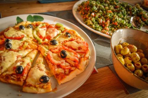 Pizza Maissa, grüne Oliven und Taboulé Salat